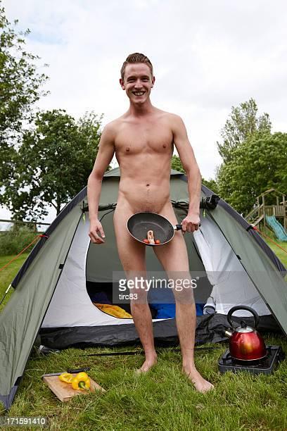 Mâle Naturiste cuisine de saucisses sur le Réchaud de camping