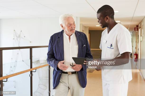 Male nurse and senior male patient discussing over digital tablet at hospital corridor