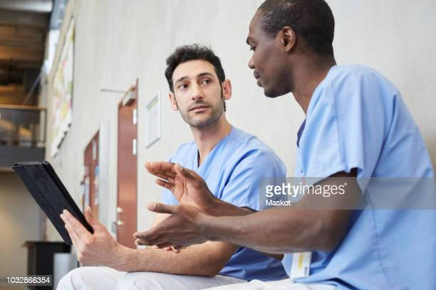 Male nurse gesturing while discussing over digital tablet with coworker in corridor at hospital