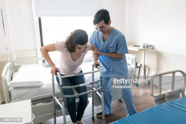 male nurse helping a young patient stand up from hospital bed while she leans on walker - injured stock pictures, royalty-free photos & images