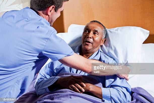 Afroamericano enfermera ayuda hombre senior paciente