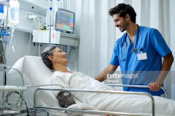 une infirmière de sexe masculin écoute un patient dans la zone de rétablissement. - infirmier photos et images de collection