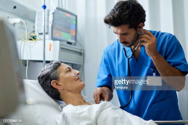 a male nurse is listening with a stethoscope a patient's chest. - respiratory system stock pictures, royalty-free photos & images