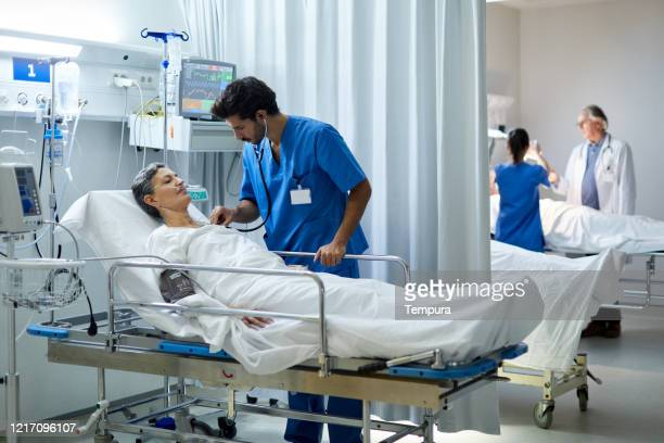 a male nurse is listening with a stethoscope the heart bit of a patient. - intensive care unit stock pictures, royalty-free photos & images