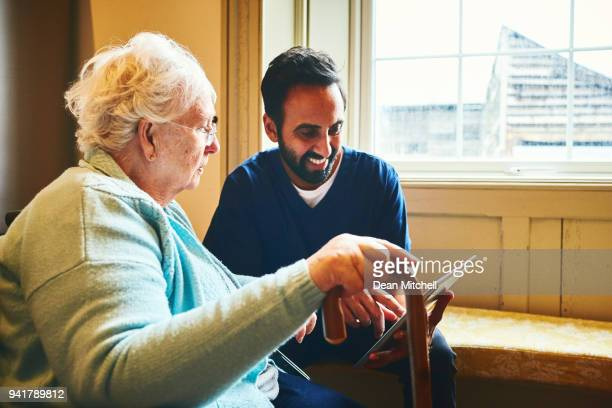 male nurse showing a digital tablet to an elderly woman - social services stock pictures, royalty-free photos & images