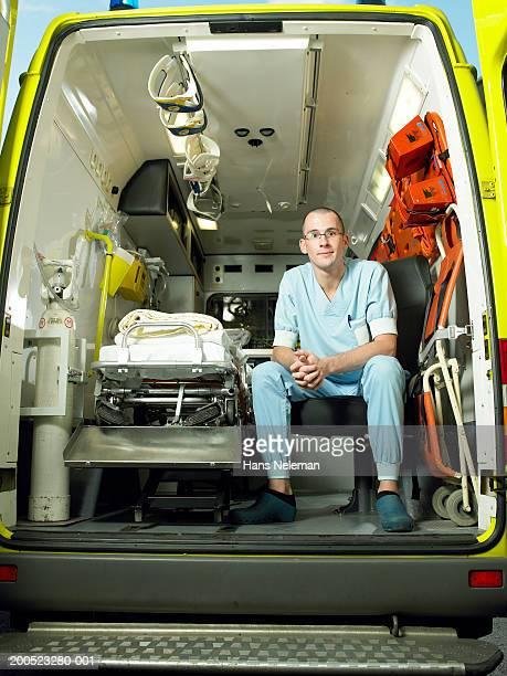 Male nurse sitting in ambulance, portrait