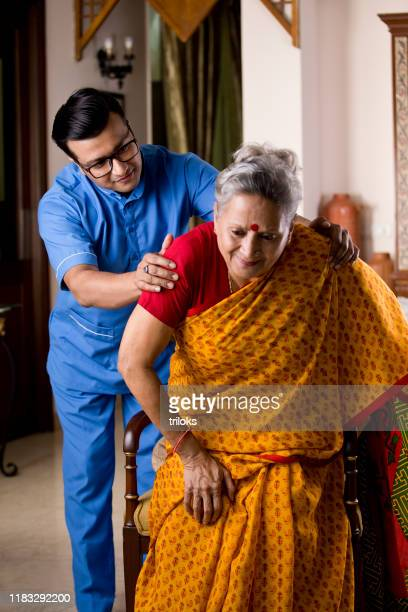 male nurse taking care of old woman suffering with knee pain - pain stock pictures, royalty-free photos & images