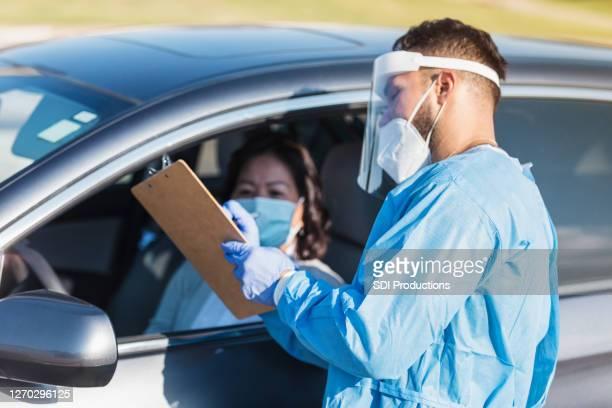 男性看護師は、covidテストラインで患者と話します - ドライブスルー検査 ストックフォトと画像