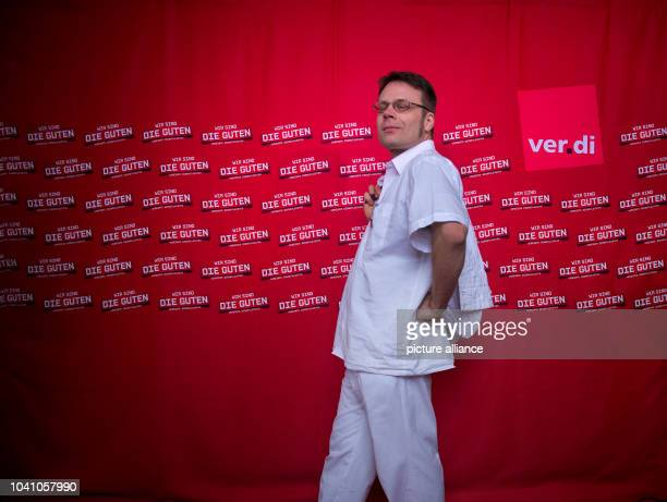 Male nurse Wolfgang Vogel symbolically poses on a red carpet at the Semperoper in Dresden Germany 21 February 2014 The United Service Sector Union...