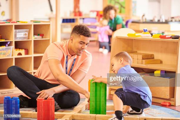 male nursery teacher - teacher stock pictures, royalty-free photos & images