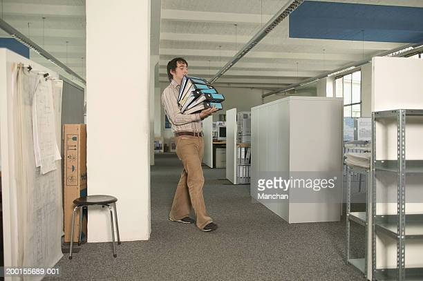 Male office worker holding stack of files