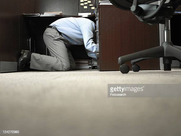 Male office worker kneeling under desk