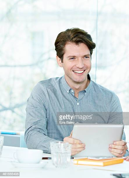 Male office worker smiling in a meeting.