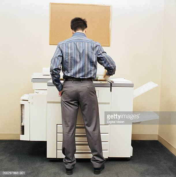 Male office worker using photocopying machine, rear view
