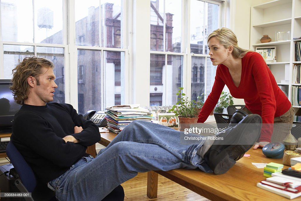 Male office worker with feet on desk, woman leaning on edge of desk : Foto de stock