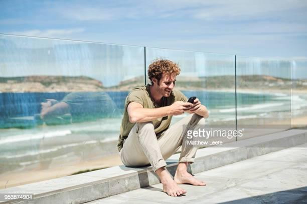 male on mobile device - チノパンツ ストックフォトと画像