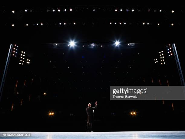 male opera singer performing solo on stage, arm raised, rear view - theatrical performance photos et images de collection