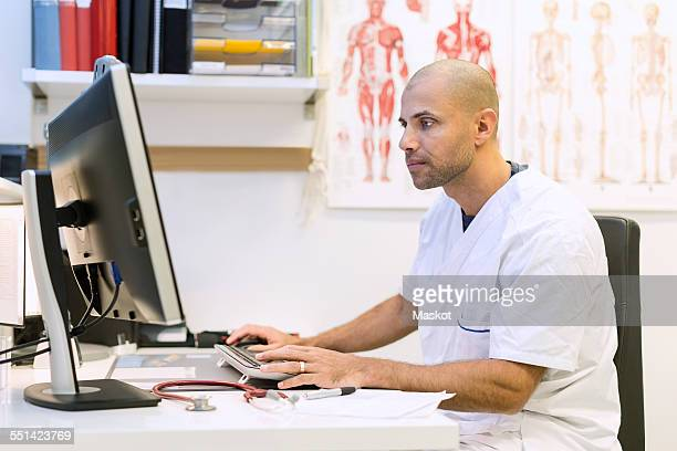 Male orthopedic doctor using computer at desk in clinic