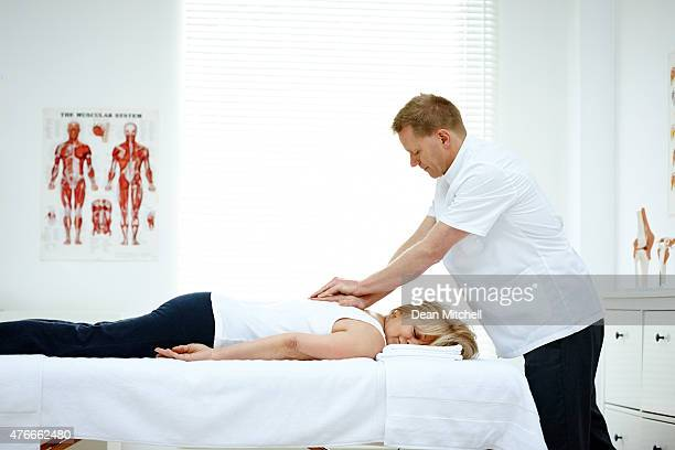 male osteopath treating back problem of a woman - osteopath stock photos and pictures