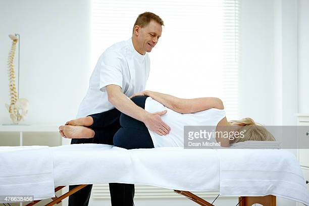 Male osteopath treating lower back problem of a woman