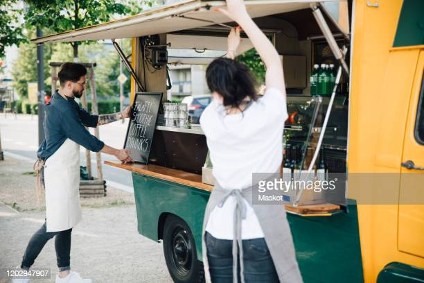 male owner adjusting board on concession stand while female coworker opening shade of food truck - small business stock pictures, royalty-free photos & images