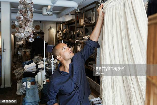 Male owner arranging jeans on shelf at clothing store