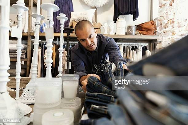 Male owner arranging jeans on table by candles at clothing store