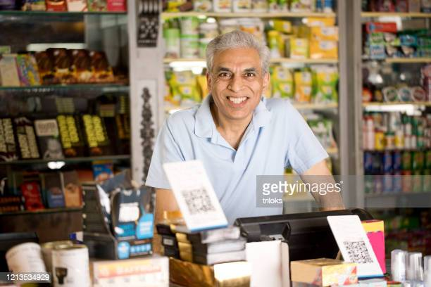 male owner at supermarket - indian ethnicity stock pictures, royalty-free photos & images