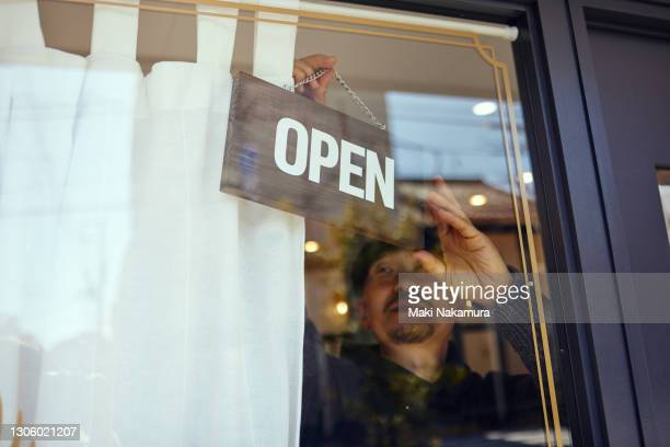 a male owner hangs an open sign on a glass door. - store opening stock pictures, royalty-free photos & images