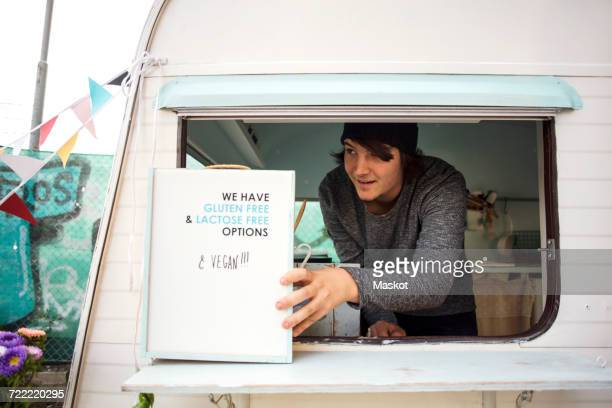 Male owner looking away while placing sign at window on food truck