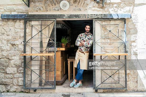 Male owner of wine bar leaning against entrance door