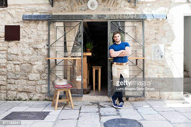Male owner of wine bar leaning outside