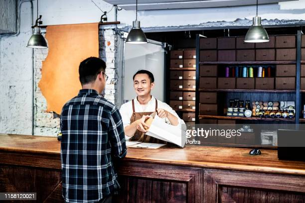 male owner packing box while talking to customer - consumerism stock pictures, royalty-free photos & images