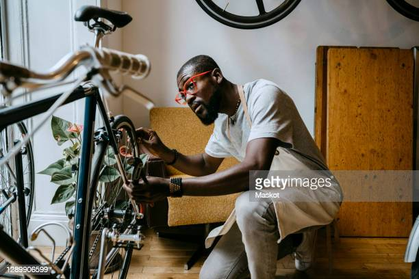 male owner repairing bicycle in workshop - owner stock pictures, royalty-free photos & images