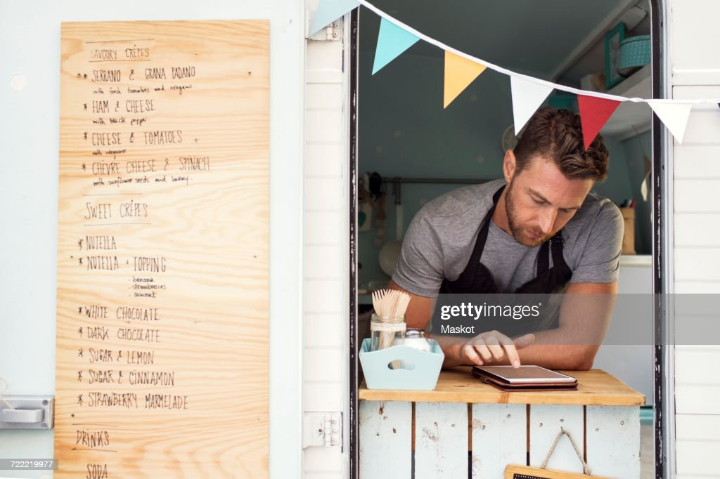 Male owner using digital tablet at food truck window : Stock Photo
