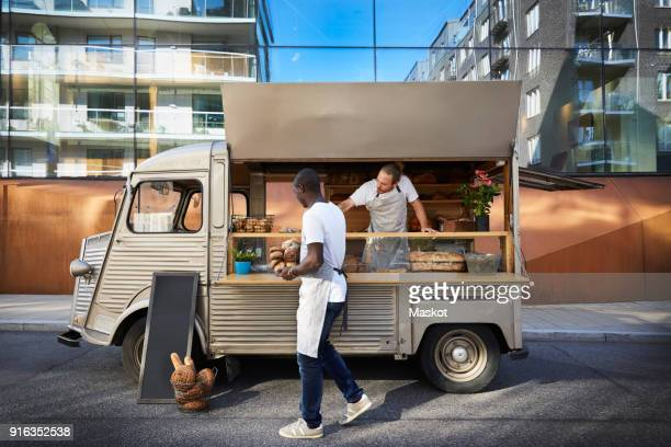 male owners working at food truck parked on city street - food truck fotografías e imágenes de stock