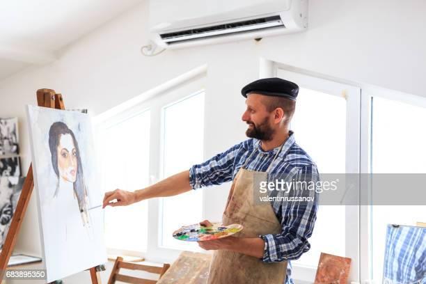 männliche maler zeichnung porträt der jungen frau in der werkstatt - malerleinwand stock-fotos und bilder