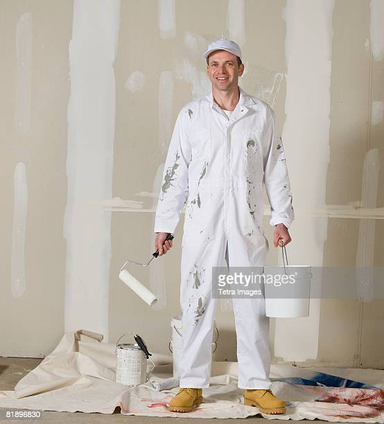 Male painter holding paint roller and paint can