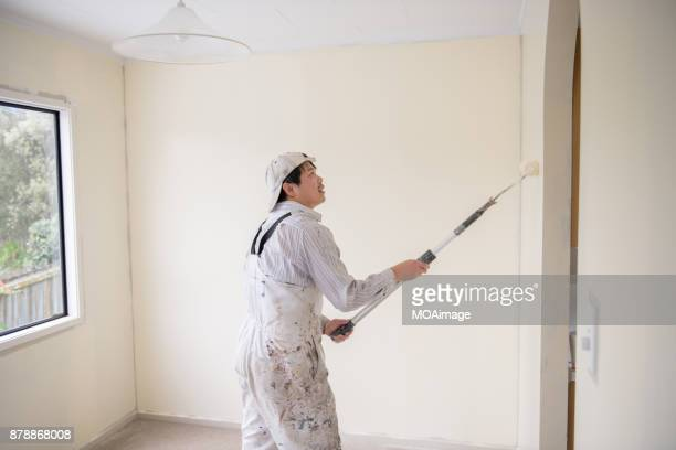 A male painter is painting the room