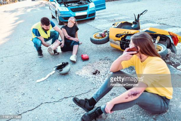 male paramedic cleaning female's leg wound while other female is calling for help - gory car accident photos stock pictures, royalty-free photos & images