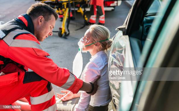 paramédico masculino ajudando ferido mulher - acidente de carro - fotografias e filmes do acervo
