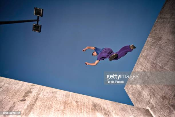 male parkour athlete jumping from a wall in a city - robb reece stock-fotos und bilder