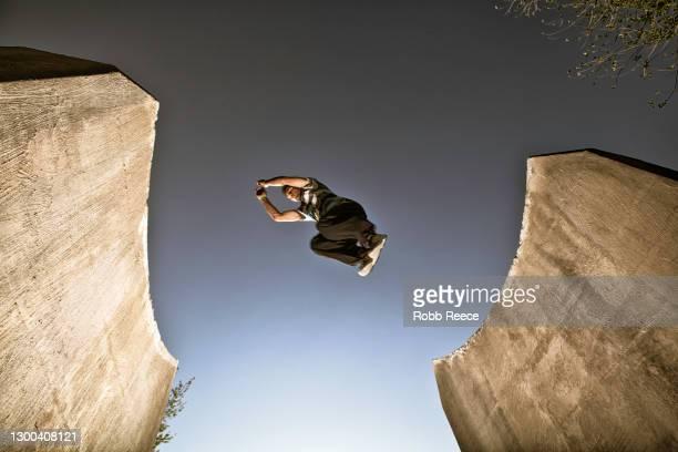 male parkour athlete jumping in a city - robb reece stock-fotos und bilder