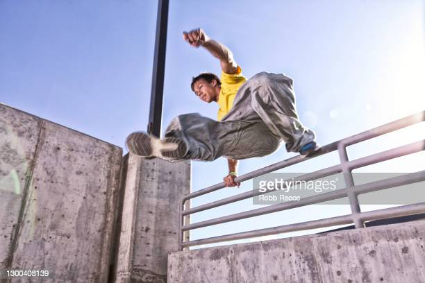 male parkour athlete jumping over a wall in a city - robb reece stock-fotos und bilder