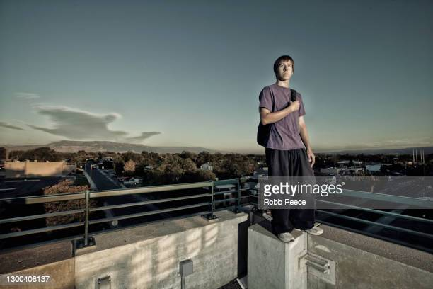 male parkour athlete standing on an edge of a building - robb reece stock pictures, royalty-free photos & images