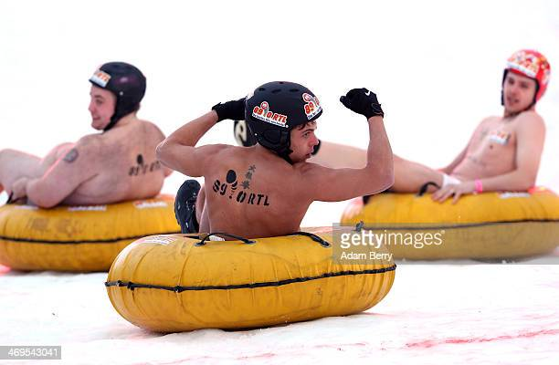 Male participants compete in the 2014 occurrence of the annual naked innertube snowsledding competition on February 15 2014 in Hecklingen near...