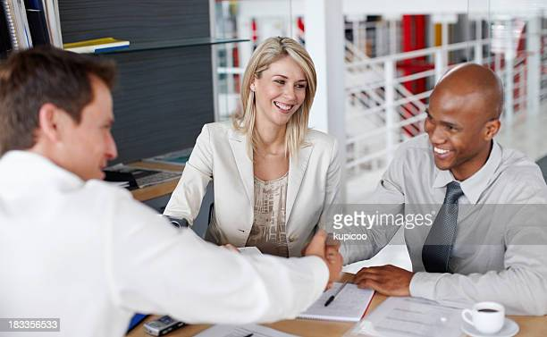 Male partners shaking hands after a business deal at desk
