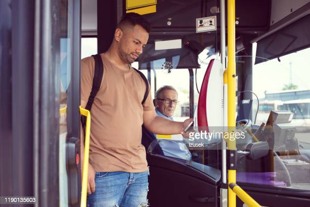 male passenger paying fare at entrance of bus - fare stock pictures, royalty-free photos & images