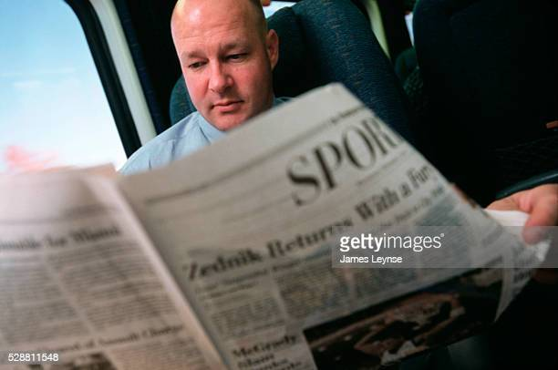 A male passenger reads a newspaper on board the trial run of the Acela express from Washington DC to Boston