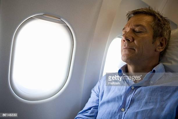 A male passenger sleeping on a plane